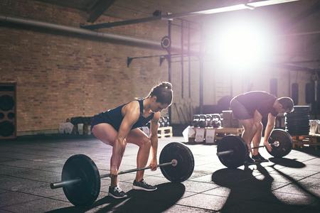 사람들은 체육관에서 무거운 역기를 들고 서서히 움직이고 있습니다. 가로 실내 촬영