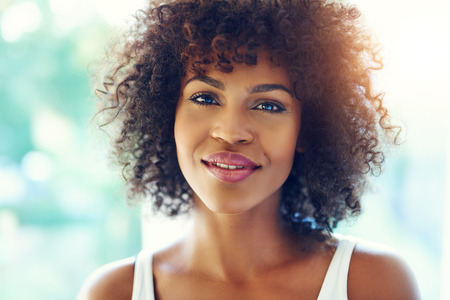 Portrait of happy young black woman relaxing in bright sunshine