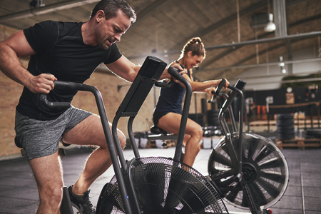 hardly: Young man and woman wearing? training hardly on cycling machines in light spacious gym.