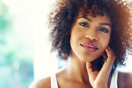 햇빛에 손과 복사본 공간에 턱을 들고 웃는 젊은 흑인 여성의 초상화