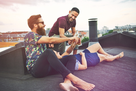merrymaking: Woman laying in lap of bearded man near friend on roof drinking bottles of beer. Copy space in sky. Stock Photo