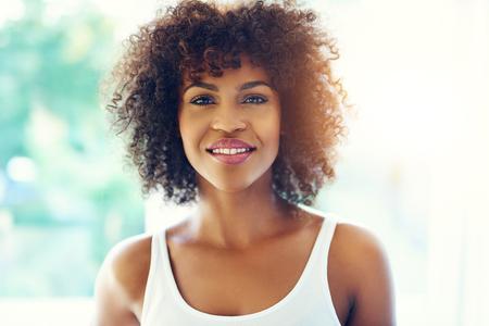 Oberkörper-Porträt des lächelnden jungen schwarzen Frau in der Sonne mit Kopie Raum Standard-Bild