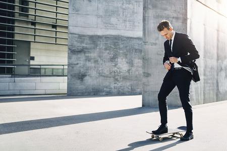 Vooraanzicht van een zakenman aanpassing van zijn stropdas over om ergens te gaan op zijn skateboard