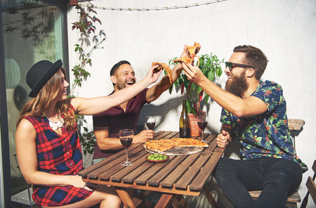 merrymaking: Friends toast with pizza and laugh while outside seated at patio table Stock Photo