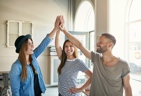 approvement: Group of three young people standing and giving gesture high five to each other in light office. Stock Photo