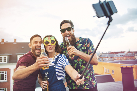 merrymaking: Group of three adults drinking and taking pictures of themselves on roof with selfie stick on roof