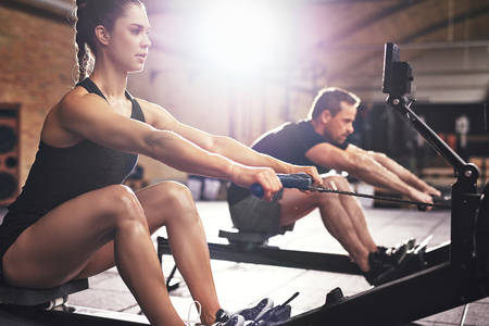 Two young sportsmen having hard workout on rowing machines in gym. Stock Photo