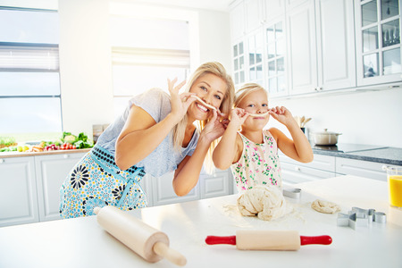adoring: Pretty blond mother and girl playing with dough in bright kitchen with rolling pins on table