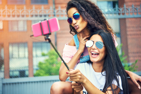 Duo of happy friends taking a self portrait outside with pink cell phone attached to selfie stick pole