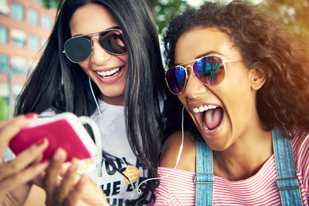 彼らは自分の携帯電話で写真を撮るとサングラスと笑顔を広く着用の女性の友人