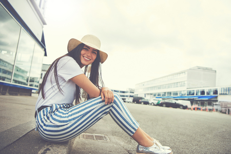 Woman seated on curb wearing striped pants smiles at camera with parked cars in the distance behind her