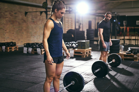 Strong people looking at heavy barbells in gym. Horizontal indoors shot