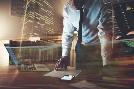 ノート パソコンやテーブルの上の携帯電話を集中して見ているドキュメントで作業する深刻なビジネス人