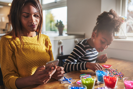 preoccupied: Preoccupied young woman in yellow checking her phone while child chooses beads from various colors on table Stock Photo
