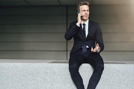 and the horizontal man: Communicative man talks cell phone. Horizontal outdoors shot