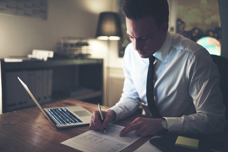 Businessman working concentrated on documents at night, working overtime at office