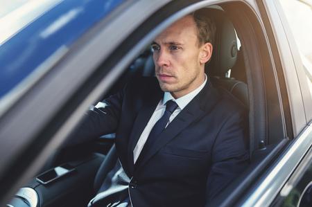 and the horizontal man: Suit wearing man looking forward while driving car. Horizontal outdoors shot. Stock Photo