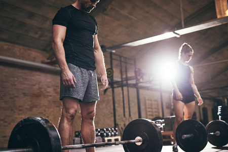 Sporty man and woman preparing to do exercise with barbells. Horizontal indoors shot Stock Photo