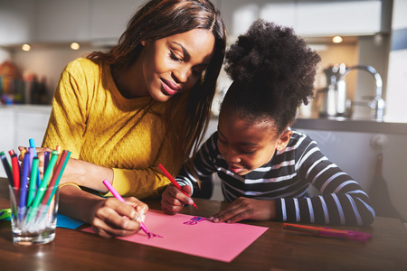 Black mother and daughter drawing in their home Imagens