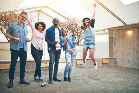 indoor inside: Young woman jumping with her arms up celebrating win in petanque game, her friends smiling, standing inside indoor petanque club Stock Photo