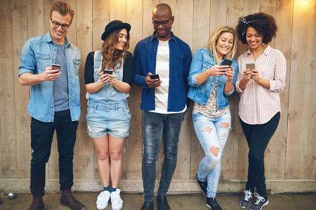 Groep van goed uitziende jonge mensen mannen en vrouwen in vrijetijdskleding staande tegen ongeverfd houten wand, kijkend naar smartphones en glimlachen Stockfoto