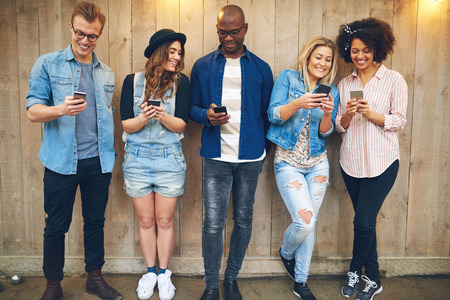 Group of good looking young people men and women in casual wear standing against unpainted wooden wall, looking at smartphones and smiling