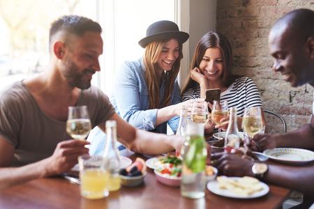 두 남성 및 두 여자의 전화 동안 뭔가 공유하는 동안 여자 맛있는 저녁 식사의 그룹. 스톡 콘텐츠