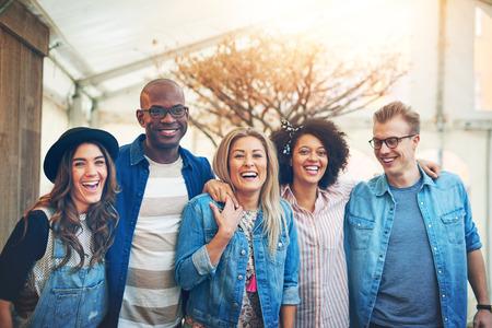 Groep van vijf mooie jonge mensen in vrijetijdskleding staande nauw samen binnen, lachen en glimlachend poseren voor de camera,