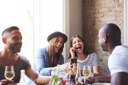 Small group of four diverse friends laughing at something on phone at dinner table in restaurant Foto de archivo