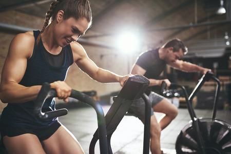 스포티 한 사람들이 체육관에서 카디오 훈련을하는 동안. 가로 실내 촬영