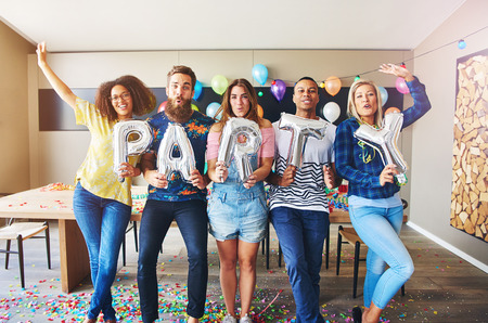 merrymaking: Diverse group of five young male and female adults with inflatable balloon PARTY signs in room Stock Photo