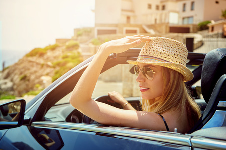 Grinning gorgeous young woman with hat and sunglasses at the steering wheel in a convertible top automobile parked near rocky hill Stock Photo