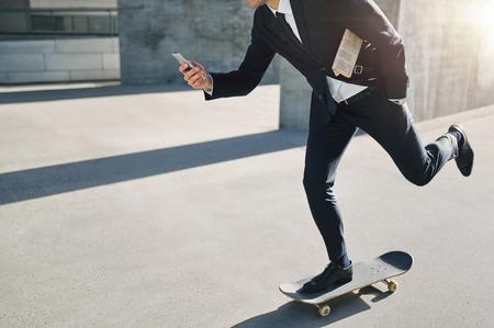 움직이는 동안 그의 전화를보고 스케이트 보드에 사업가의 전면 뷰 스톡 콘텐츠