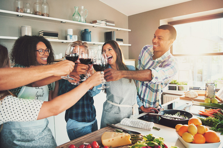 tasteful: Group of young cheerful friends cheering with wine glasses while cooking some tasteful food at kitchen. Stock Photo