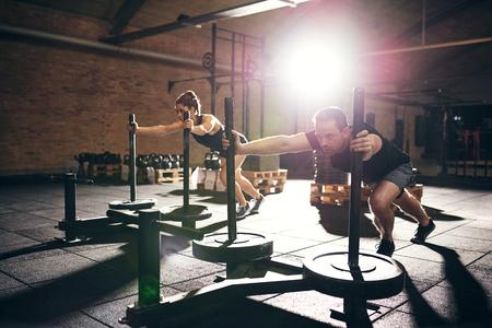 근육 질의 남자와 여자 체중 디스크와 하드 bogie 추진. 가로 실내 촬영