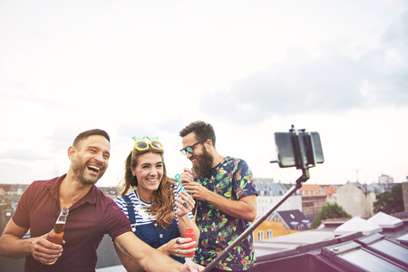 merrymaking: Three happy friends taking pictures of themselves on roof while drinking beer and blowing bubbles