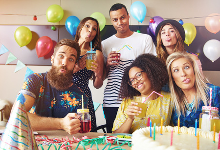 inebriated: Goofy friends pulling silly faces while partying celebrating a birthday with festive party balloons and decorations