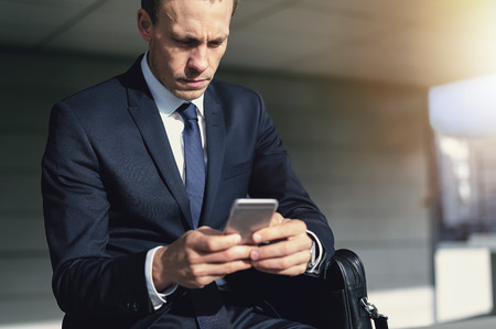office use: Confident handsome businessman using his phone. Horizontal indoors shot