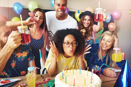 Jonge vrouw die met oogglazen op cakekaarsen blaast terwijl de vrienden zich rond haar bevinden om een ??verjaardag of het werkverjaardag te vieren Stockfoto