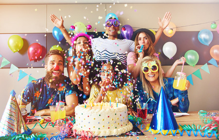 Scattered confetti falling around group at party with birthday cake and cone hats on table in foreground Stockfoto