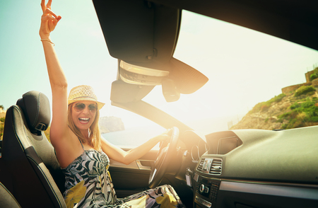 Excited woman gesturing with hand while driving her luxury retractable top automobile in summer Stock Photo