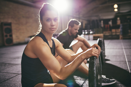heavy weight: Two young sportive people having rest while sitting on floor with heavy weight disks in light gym.