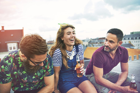 merrymaking: Laughing group of barefoot men and woman drinking beer while sitting on roof outdoors with copy space in sky Stock Photo