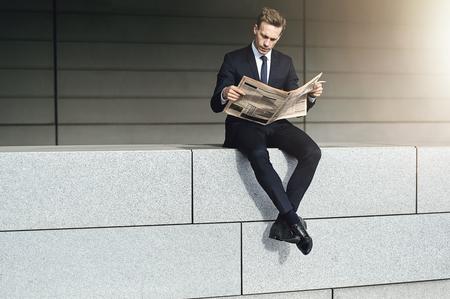 クールなビジネスマンが新聞でレンガの壁に座っています。