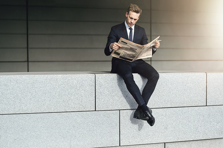 Cool businessman sits on a brick wall with newspaper Banque d'images