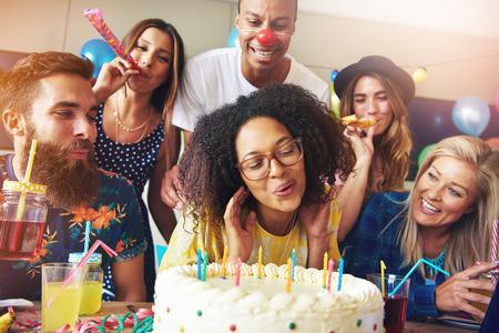誕生日や記念日のお祝いのためのテーブルで友人に囲まれながらのケーキの上の蝋燭を吹いて幸せな女 写真素材