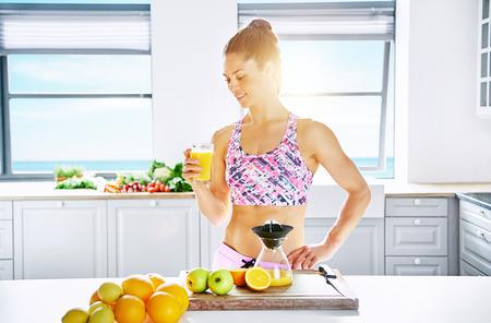 mujer deportista: La mujer sana joven de pie en la luz del sol con un vaso de jugo de naranja. horizontal tiro