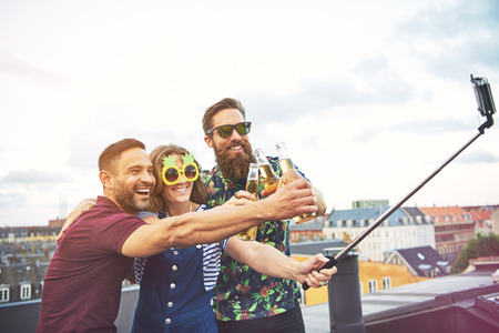 merrymaking: Inebriated goofy young friends posing for a selfie laughing and joking and raising their bottles of alcohol at a rooftop party Stock Photo