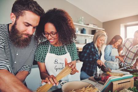 함께 부엌에서 파스타 저녁 식사를 준비하는 좋은 친구의 혼합 된 그룹. 그들의 앞에 이젤에 요리 책. 스톡 콘텐츠
