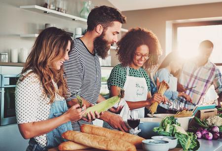 Gute Freunde lachen und reden, während Mahlzeiten am Tisch voller Gemüse und Nudeln bereit für das Kochen in der Küche vorbereitet